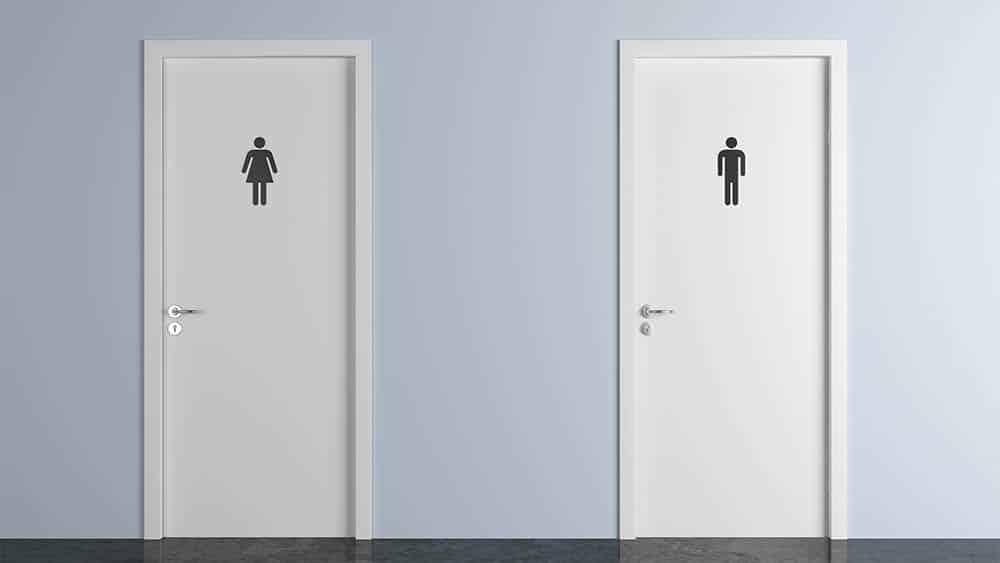 Portas de banheiro lado a lado, com placa masculino e feminino. Preconceito faz pessoas trans evitarem banheiro, o que aumenta o risco de infecção urinária
