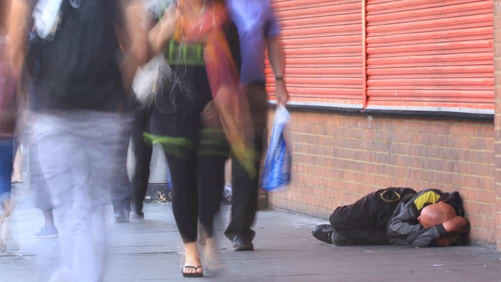 Homem em situação de rua deitado em calçada com pessoas passando ao largo.