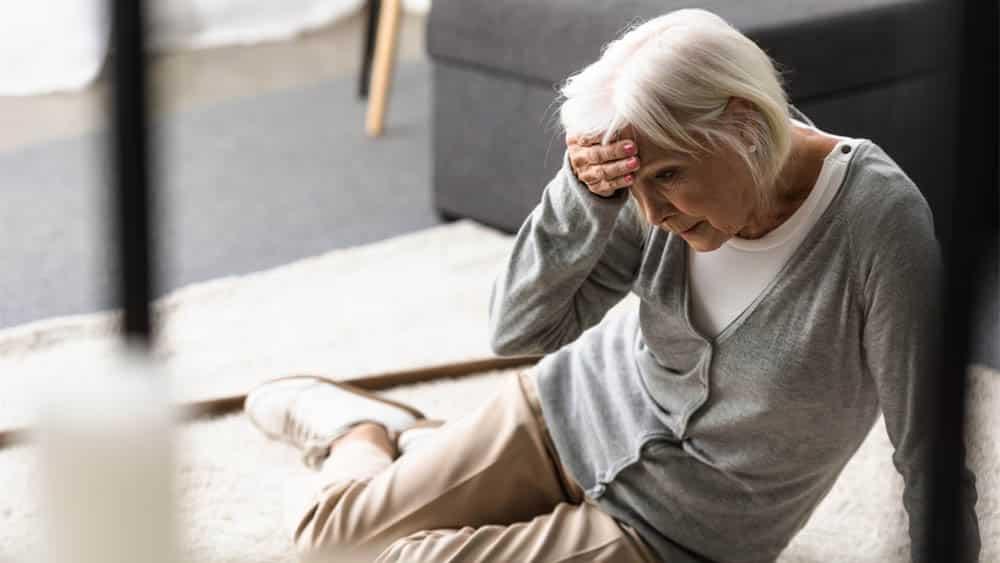 Idosa sentada no chão com mão na testa indicando vertigem, principal sintoma da vertigem posicional paroxística benigna (VPPB).