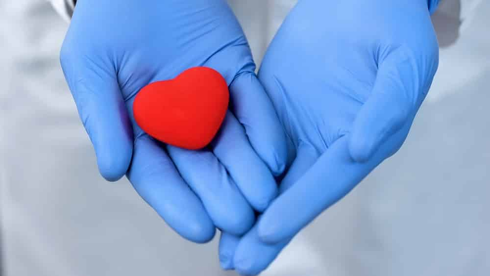 Duas mãos com luvas segurando um coração. Imagem-conceito de doação de órgãos.