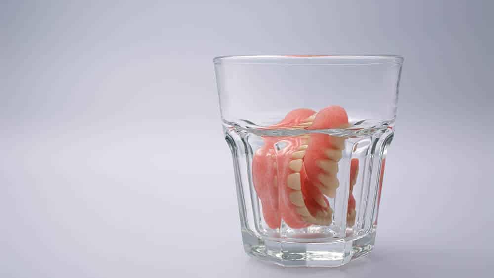 Copo contendo água e dentadura.