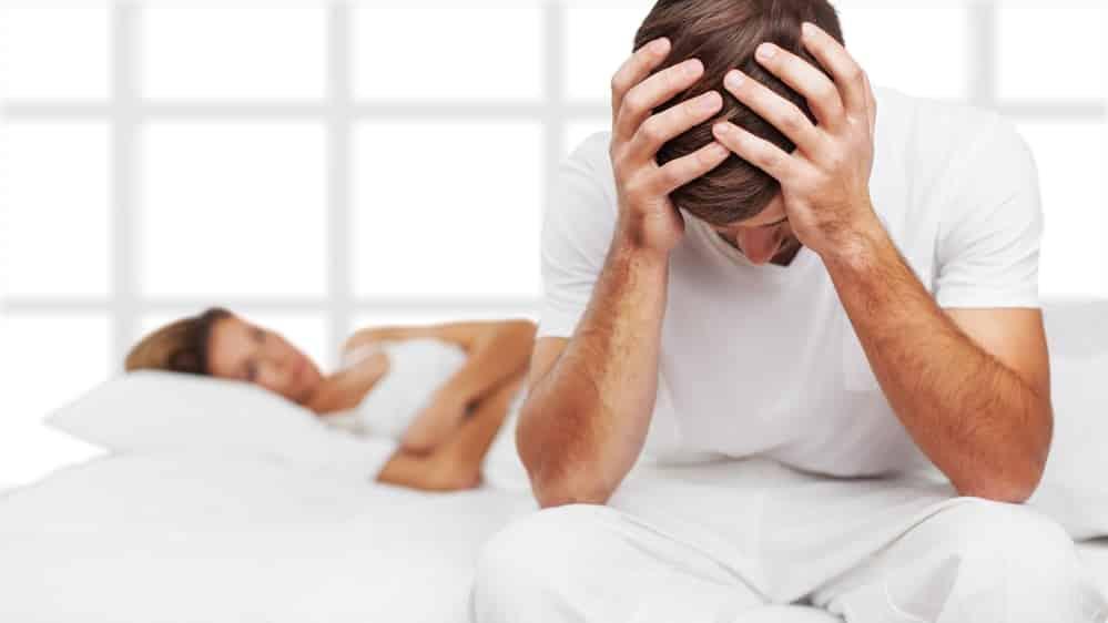 homem sentado na beira da cama, com cabeça escondida nas mãos, ao lado de mulher deitada; conheça a história de Paulão, o patriota