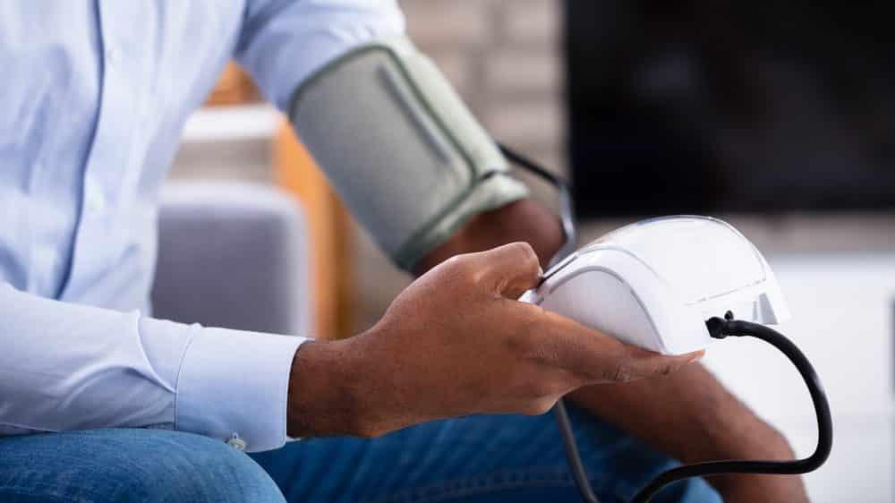 homem sentado no sofá medindo a pressão. Pressão alta em geral não causa sintomas
