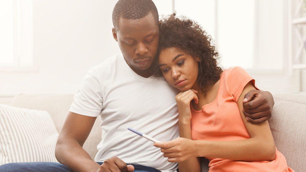 Casal triste diante de teste de gravidez negativo. Veja algumas das causas frequentes de infertilidade.