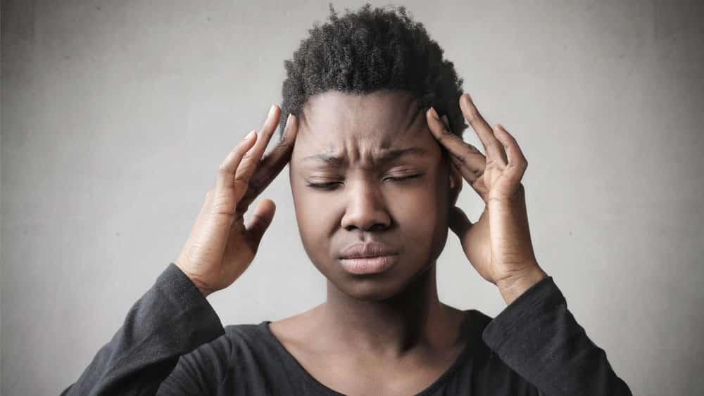 Mulher negra com dor de cabeça