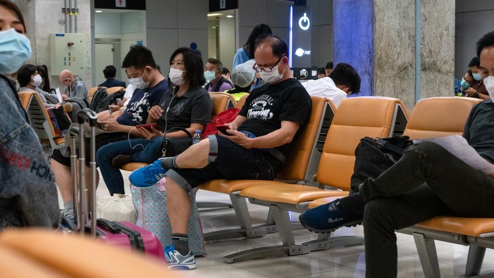 pessoas aguardam em aeroporto de Pequim usando máscaras para evitar a contaminação pelo Covid-19