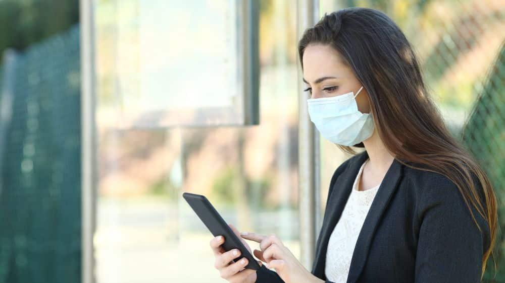 Mulher com máscara contra coronavírus olhando celular em ponto de ônibus.