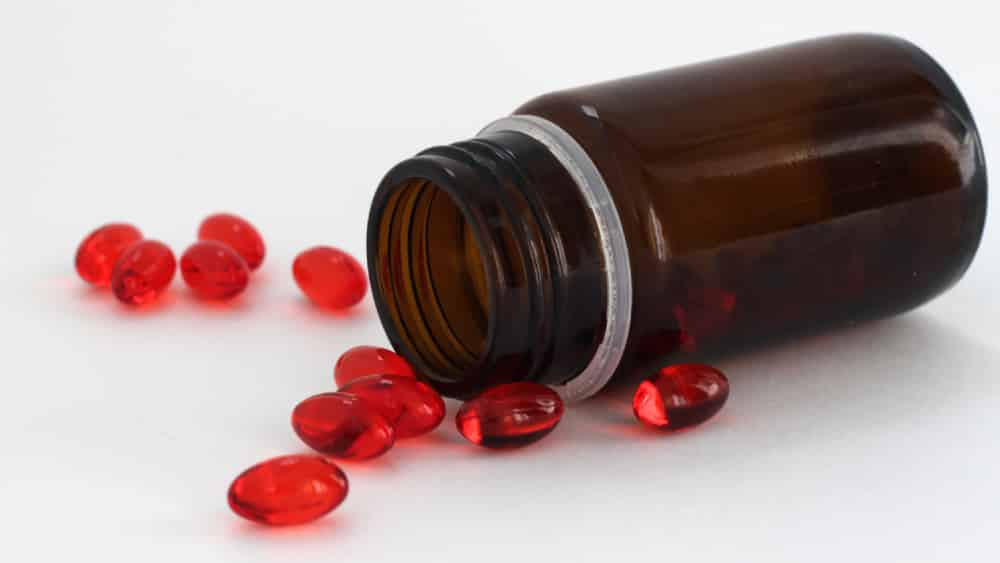 Pote de ibuprofeno caído com cápsulas vermelhas de gel espalhadas ao redor.