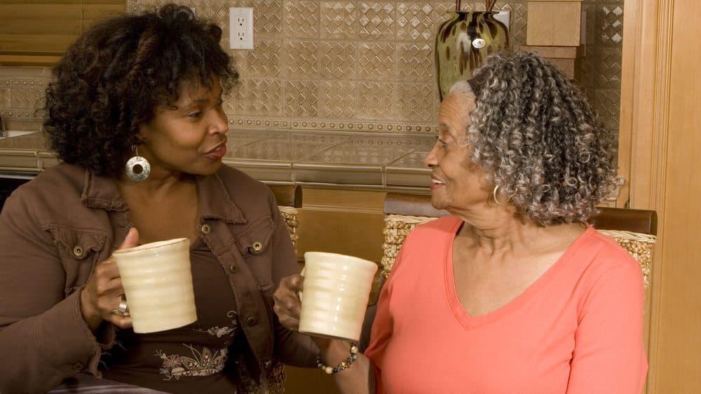 mulher adulta e mãe idosa tomam café. Idosos são mais vulneráveis ao coronavírus