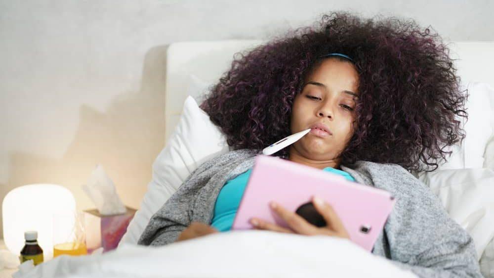 menina doente deitada, com termômetro na boca. Veja o que fazer com pessoa com suspeita de coronavírus