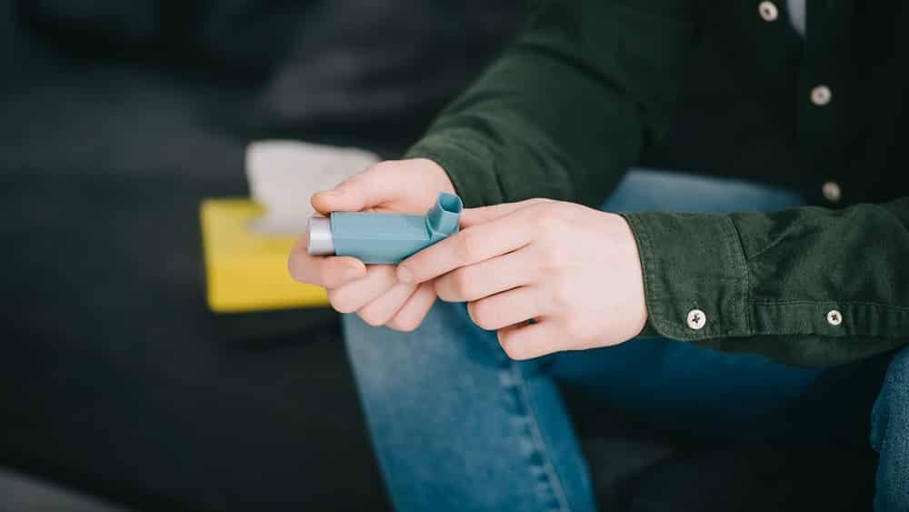close em mão segurando bombinha. veja diferença entre asma e coronavírus
