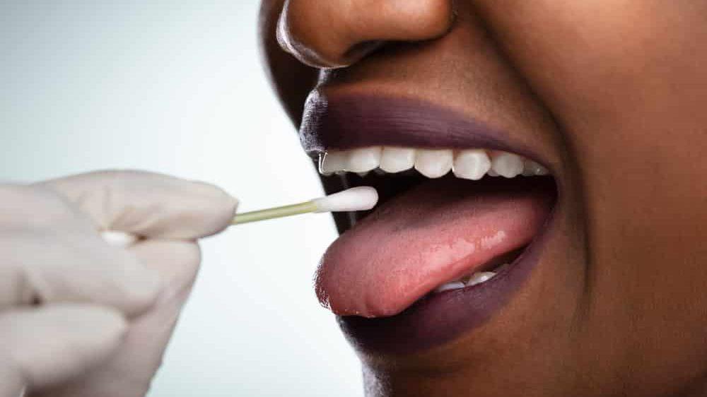enfermeira colhe teste coronavírus na boca de paciente