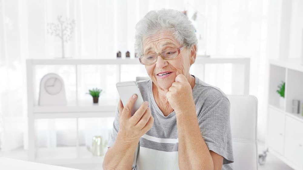 mulher idosa olha celular. saúde mental dos idosos na quarentena pode ser afetada