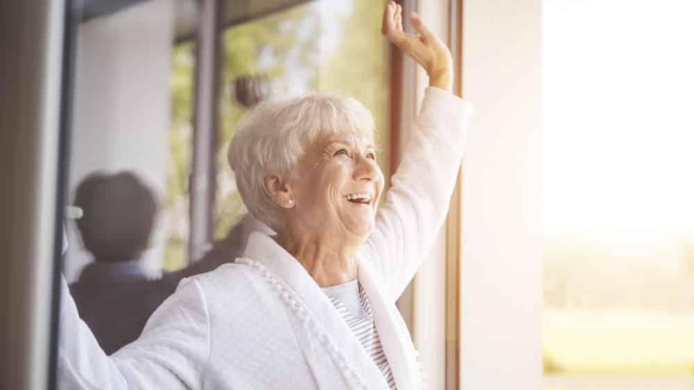 mulher toma sol na janela. não há benefício na suplementação de vitamina D para covid-19