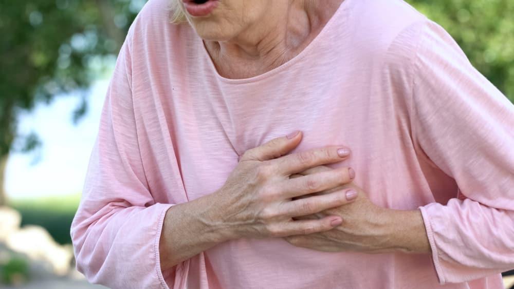 mulher idosa com mão no peito. infarto nas mulheres tem aumentado
