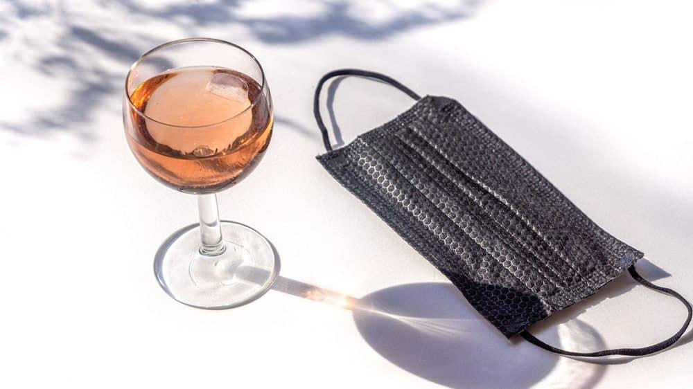 copo de vinho e máscara preta sobre a mesa ao ar livre. Uso de álcool na quarentena pode ser abusivo