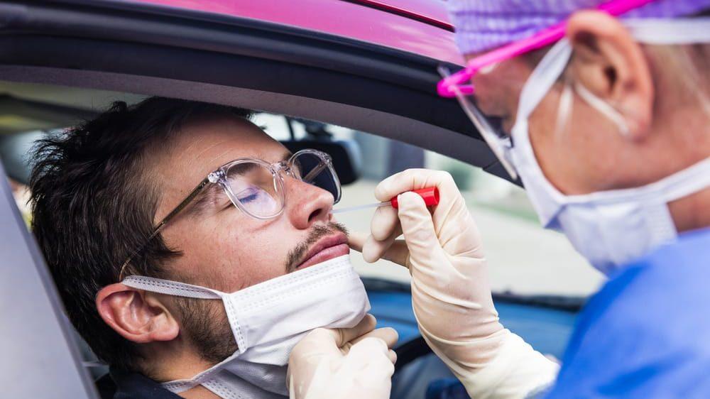 enfermeira colhe secreção nasal de paciente em carro para realizar exame. Testes para o novo coronavírus estão disponíveis em laboratórios