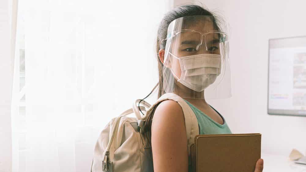 menina de máscara e proteção facial carrega mochila e caderno para a volta às aulas na pandemia