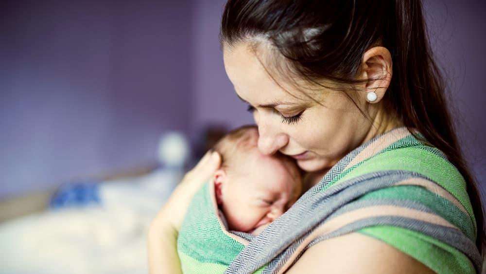mã segura recém-nascido junto ao peito. Puerpério na pandemia pode ser ainda mais difícil.