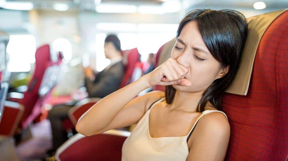 mulher sentada em condução tosse. Transmissão do novo coronavírus pode se dar pelo ar