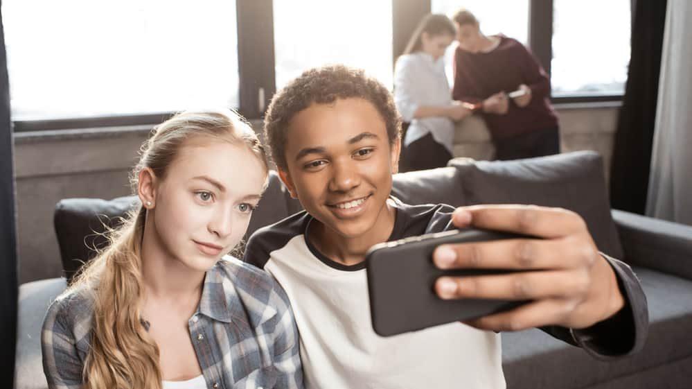 casal de adolescentes tiram selfie.Estudo revela impacto das mídias sociais na saúde mental.