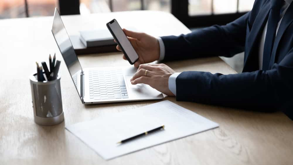 close de homem sentado à mesa de escritório diante do computador e do celular. Vida virtual ficou mais intensa com a pandemia