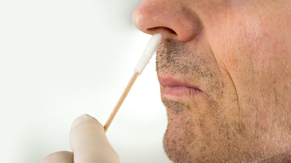 close em rosto de homem recebendo swap no nariz para realizar teste para covid-19