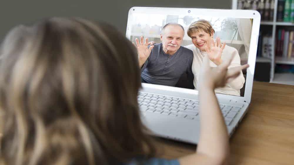 criança de costas acena para avós na tela do computador. Festas de fim de ano devem ser suspensas por causa da covid-19