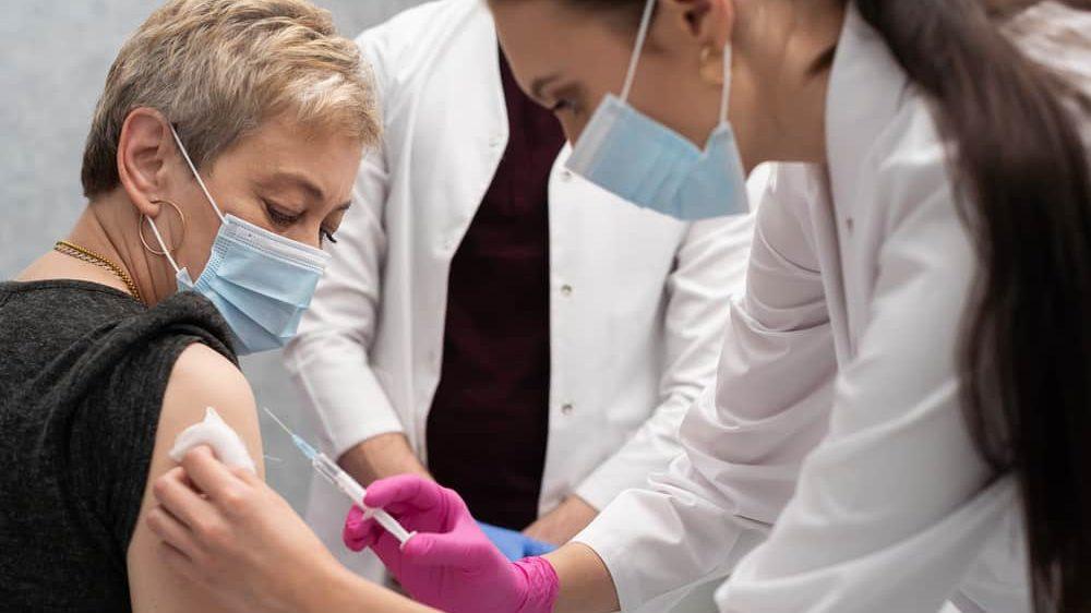 enfermeira aplica a vacina do Butantan em mulher idosa