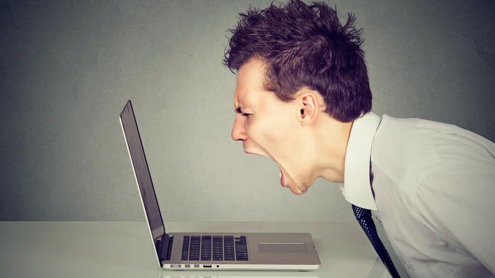 homem com ódio grita em frente à tela do computador