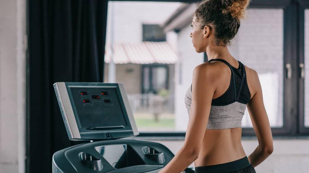 mulher de costas em esteira ergométrica. Atividade física altera metabolismo e previne doenças