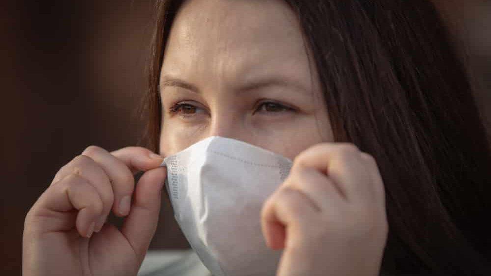 close em rosto de mulher com máscara. nova variante inglesa do coronavírus pode ser mais contagiosa