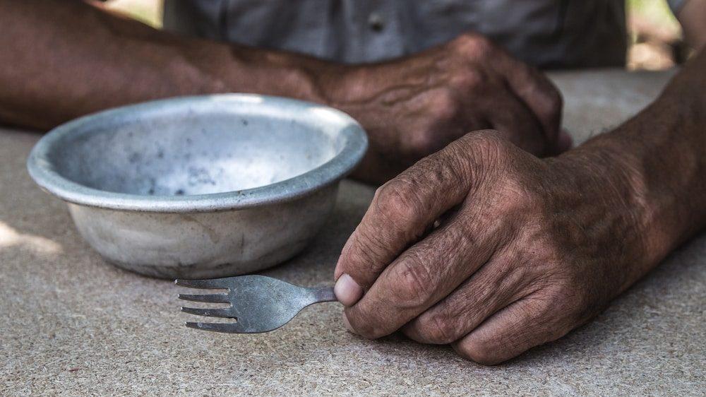 close em mãos de homem segurando garfo, apoiadas em mesa com prato vazio. epidemia causou a fome de milhares de brasileiros