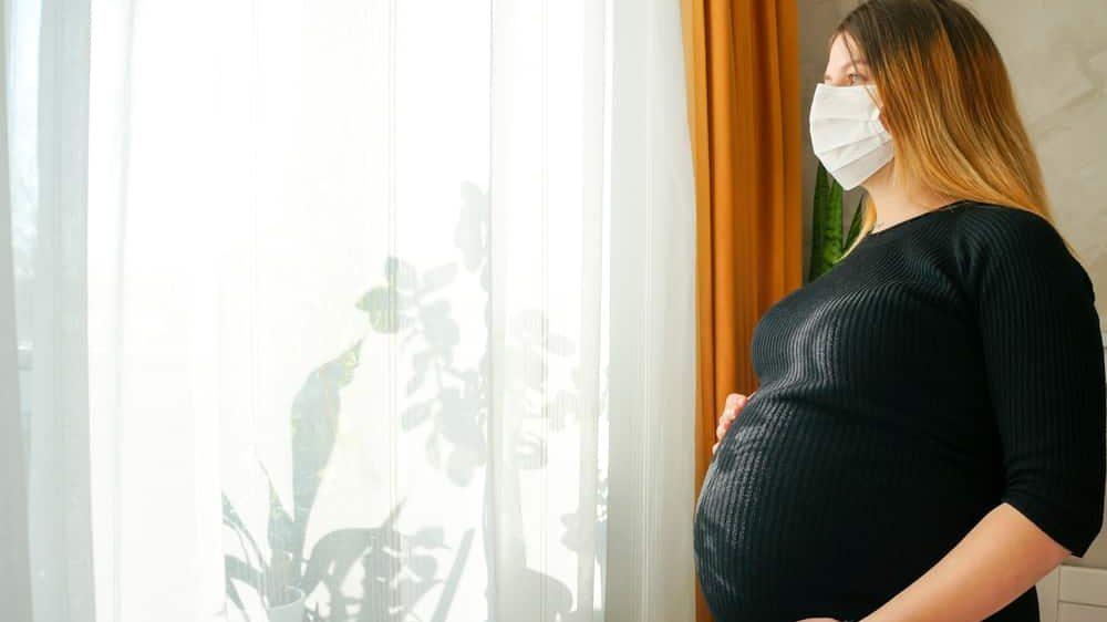 mulher grávida de máscara olha pela janela de casa. veja a relação entre coronavírus e gravidez
